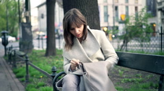 Young woman searching for her phone in handbag sitting on bench in park Stock Footage