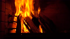 Burning firewood in the corner of a brick fireplace 4K video - stock footage