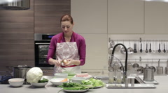 A woman cleans the kitchen knife onion - stock footage