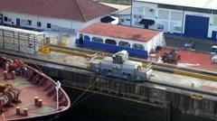 Train mules pulling cargo ship through Gatun lock of Panama Canal, Panama Stock Footage