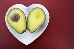 Avocado cut in half on heart shape plate - stock photo