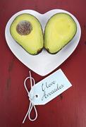 Avocado cut in half on heart shape plate Stock Photos