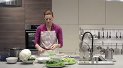 Woman in kitchen with a knife to clean the carrots Stock Footage