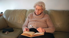 Eighty year old lady holding magnifying glass and reading an old book - stock footage