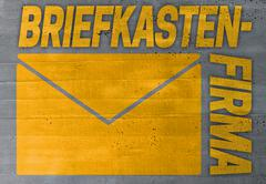 Briefkastenfirma (in german offshore company) concept on cement texture backg Stock Photos
