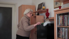 Active grandmother dusting a bookshelf, doing chores and cleaning the house - stock footage