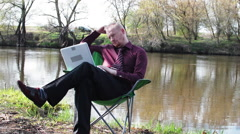 Businessman Sitting Sad With a Tablet and is Forced to Work For Camping by the - stock footage