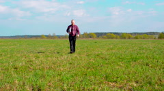 Tired Businessman Walking on the Field With the Laptop - stock footage