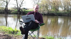Businessman Sitting With a Tablet and is Forced to Work For Camping by the - stock footage