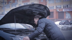 Man repairing his car on road Stock Footage