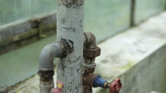 Rusty pipe tap in a greenhouse Stock Footage