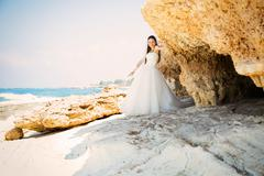 Outdoor portrait of young beautiful woman bride in wedding dress on beach Kuvituskuvat