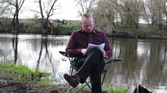 Businessman Sitting With a Tablet and Papers and is Forced to Work For Camping - stock footage