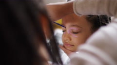 Young girl getting her face painted by another child, in slow motion Stock Footage