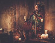Old medieval king with goblet of wine on the throne in ancient castle interio - stock photo