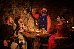 Medieval people eat and drink in ancient castle tavern. Stock Photos