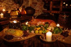 Medieval ancient kitchen table with typical food in royal castle. Stock Photos