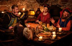 Medieval people eat and drink in ancient castle kitchen interior. - stock photo