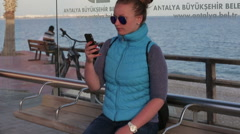 Beautiful girl writes sms smartphone use Stock Footage