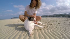 Happy Woman Playing with Her Pet Dog at Beach. UHD. Stock Footage
