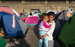 Syrian boy with little sister in her arms in a tent camp for refugees Kuvituskuvat