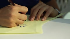 A close view of a child hands painting on white paper at school. Stock Footage