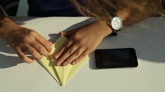 A close view of a child hands making origami of yellow paper at school. - stock footage