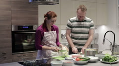 Family cuts vegetables in the kitchen Stock Footage