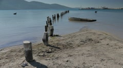 Old wooden berth stumps into the sandy sea floor with new port on the background Stock Footage