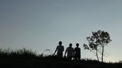 Three women on a hill walking in silhouette Stock Footage