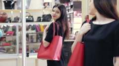 Beautiful girl in a shop trying on a red bag. A woman looking in the mirror and Stock Footage