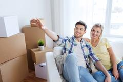 couple with boxes moving to new home and dreaming - stock photo
