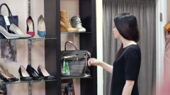 Beautiful girl in a shop trying on bag. A woman looking in the mirror and trying Stock Footage