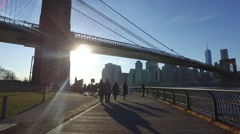 People walking under the Brooklyn Bridge on a beautiful sunny day Stock Footage