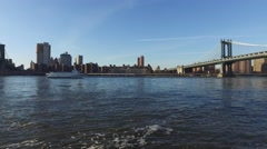 Handheld shot of East river and Manhattan bridge with boat Stock Footage