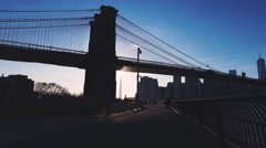 Walking under the Brooklyn Bridge while sunset Stock Footage