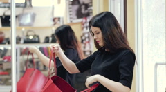 Beautiful girl in a shop trying on a red bag. Black dress. The girl is reflected Stock Footage