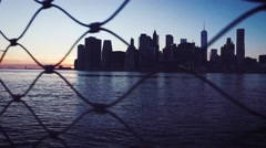 Moving next to the metal fence with downtown Manhattan skyline as background - stock footage