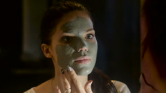 Girl smears face with a mask of clay.  Medical mask smeared on the face of the Stock Footage