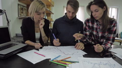 Young man draws a graph with colored pencils, explains something to the female Stock Footage