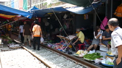 People walking at the train track of the Maeklong Railway Market Stock Footage