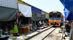 Train passing by at the Maeklong Railway Market Stock Footage