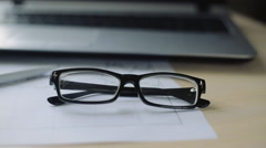 eyeglasses and pen lie on business charts. close up - stock footage