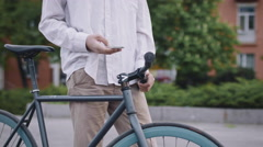 Young Guy With Long Hair Fixed Gear Bike Standing In City And Using Smartphone Stock Footage