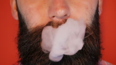 Man with a beard smoking an e-cigarette Stock Footage