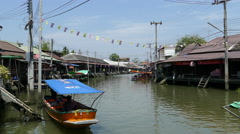 Canel with a boat passing by at the Tha Kha Floating Market Stock Footage