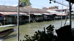 The Tha Kha Floating Market with a speeding boat passing by Stock Footage