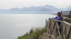 Beautiful girl standing on the waterfront in the background mountins Stock Footage