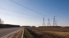 electricity transmission pylon silhouetted against blue sky - stock footage