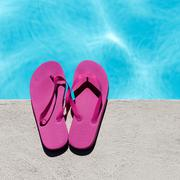 Pink slippers near swimming pool - stock photo